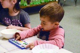 A pre-K student uses watercolors to make a segment for The Very Hungry Caterpillar.