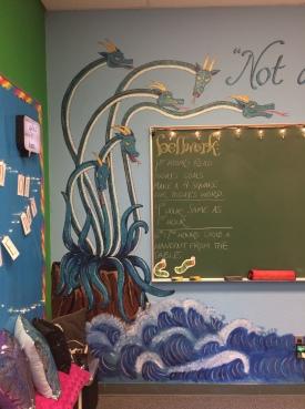 Scylla threatens a chalkboard.