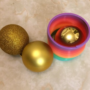 Rainbow Slinky toy and gold Christmas ornaments