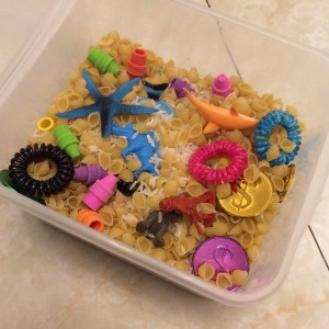 Sensory bin filled with rice, pasta, and toys
