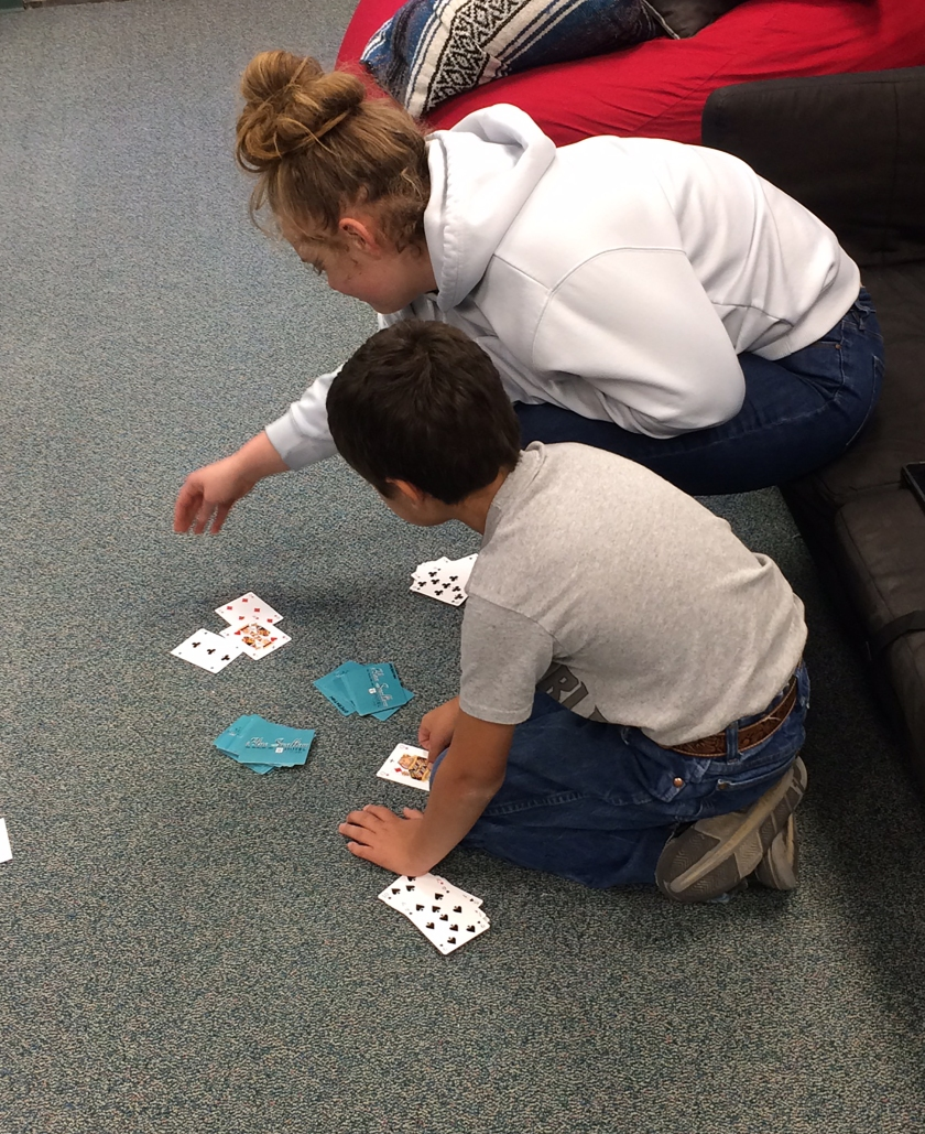 Teenager playing a math card game with a younger child